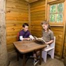 two children inside summer log cagin